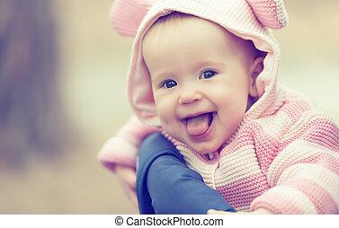 Feliz niña sonriente con capucha rosa con orejas