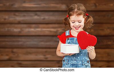 Feliz niña sonriente con regalo de San Valentín, de madera