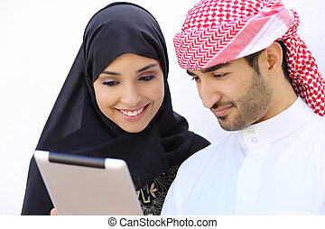 Feliz pareja árabe saudi buscando una tableta juntos