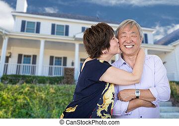 Feliz pareja adulta china besándose frente a la casa de costumbres.