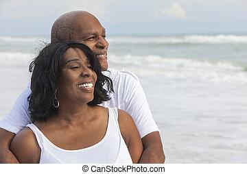 Feliz pareja afroamericana de último año en la playa