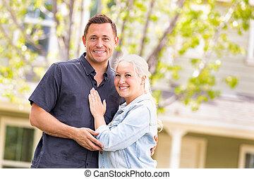 Feliz pareja caucásica en frente de la casa