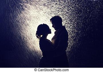 Feliz pareja de amantes en la luz trasera