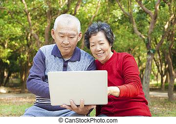 Feliz pareja de ancianos asiáticos con portátil