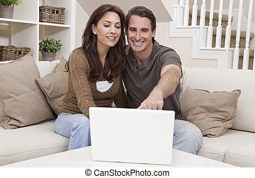Feliz pareja de hombres de mediana edad con computadora portátil