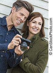Feliz pareja de hombres de mediana edad usando cámara