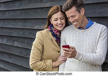 Feliz pareja de hombres de mediana edad usando celular