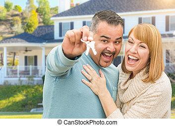 Feliz pareja de raza mixta frente a casa con nuevas llaves