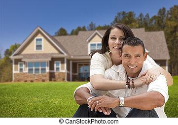 Feliz pareja hispana frente a su nuevo hogar