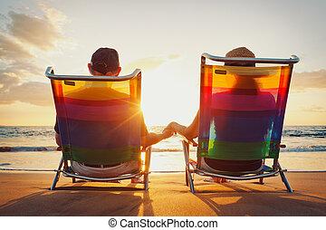 Feliz pareja romántica disfrutando de la hermosa puesta de sol en la playa