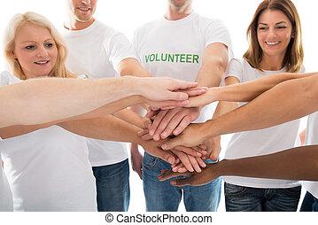 Feliz voluntarios multiétnicos apilar manos