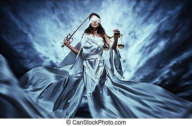 Femida, Diosa de la Justicia, con escamas y espada con los ojos vendados contra el dramático cielo tormentoso