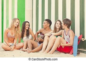 Fiesta en la playa con adolescentes y guitarra