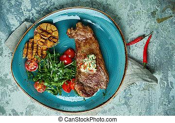 Filete con verduras y ensalada, con ajo asado