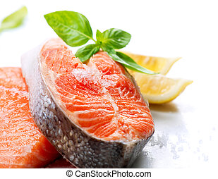 Filete de salmón rojo con hierbas y limón aislado en blanco