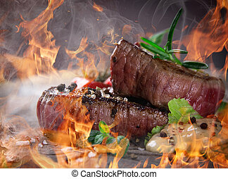 Filetes a la parrilla con llamas de fuego