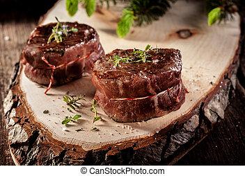 Filetes de carne de venado servidos en madera rústica