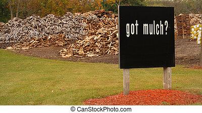 """¿Firmar frente a grandes pilas de madera diciendo: """"¿Tienes Mulch?"""""""