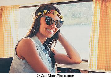Flor de niño al sol. Una joven feliz sonriendo a la cámara mientras se sienta dentro de la camioneta retro