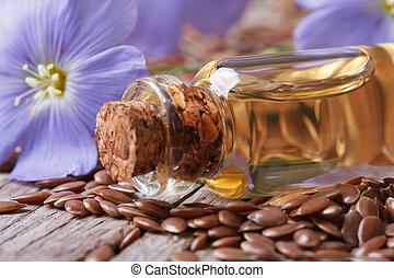 Flores y semillas de lino, aceite en macro de botella de vidrio