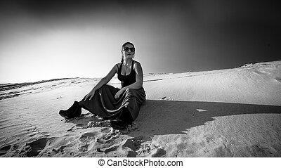 Foto de mujer cansada sentada en la duna de arena