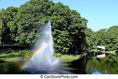Fuente con un arco iris en el canal del río Riga