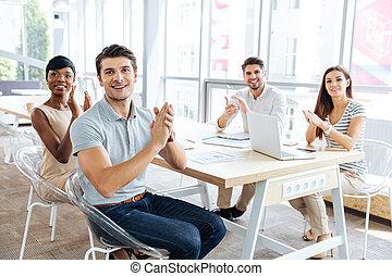 Gente alegre de negocios sentada en la presentación en la oficina y aplaudiendo