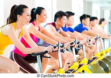 Gente asiática entrenando en el gimnasio