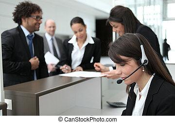 Gente de negocios agrupándose en el área de recepción de su compañía