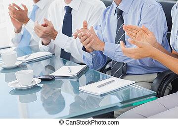 Gente de negocios aplaudiendo en la sala de juntas