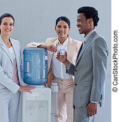 Gente de negocios con un refrigerador de agua en la oficina