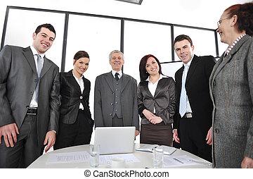 Gente de negocios de pie en la oficina y sonriendo