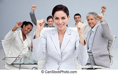 Gente de negocios feliz celebrando un éxito con las manos en alto