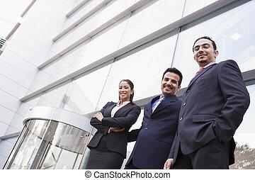 Gente de negocios fuera del edificio de oficinas