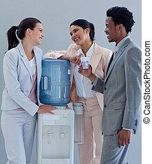 Gente de negocios hablando al lado de un refrigerador de agua