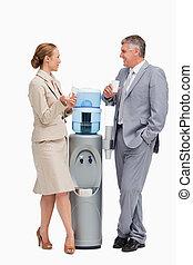 Gente de negocios hablando al lado del dispensador de agua