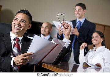 Gente de negocios hispanas en la sala de juntas sonriendo