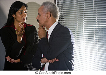 Gente de negocios multiétnica teniendo una conversación discreta en la esquina de la sala de reuniones