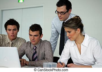 Gente de negocios sentada en una laptop
