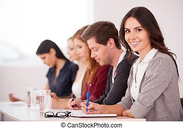 Gente en el seminario. Una joven atractiva sonriendo a la cámara mientras se sienta con otra gente en la mesa