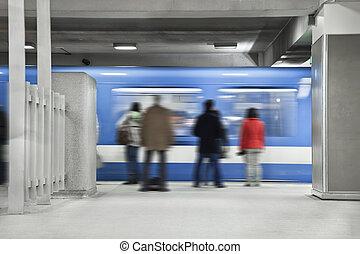 Gente esperando al metro para detenerse