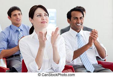 Gente internacional de negocios aplaudiendo en una conferencia