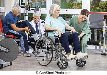 Gente mayor siendo asistida por fisioterapeutas en el centro de rehabilitación