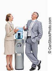 Gente riéndose junto al dispensador de agua
