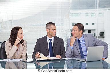 Gente seria de negocios hablando juntos mientras esperan una entrevista en la oficina brillante