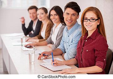 Gente trabajando juntas. Un grupo de jóvenes sentados juntos en la mesa y sonriendo a la cámara