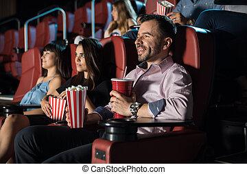 Gente viendo una película y comiendo palomitas