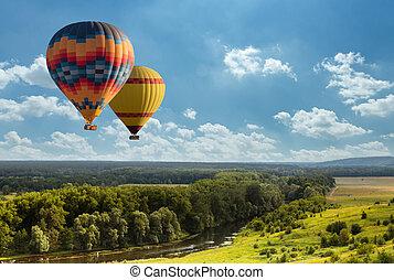 Globo de aire caliente colorido volando sobre el campo verde