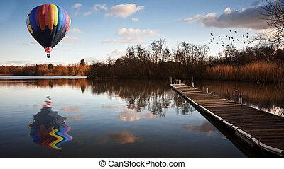Globo de aire caliente sobre el lago del atardecer con jetty