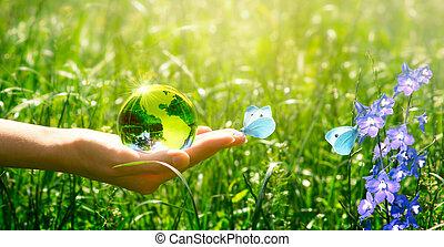 Globo de cristal de la Tierra y mariposa en la mano sobre hierba y flores de campanilla. Salvar el medio ambiente y limpiar el concepto de planeta verde. Tarjeta para el concepto del día de la Tierra.